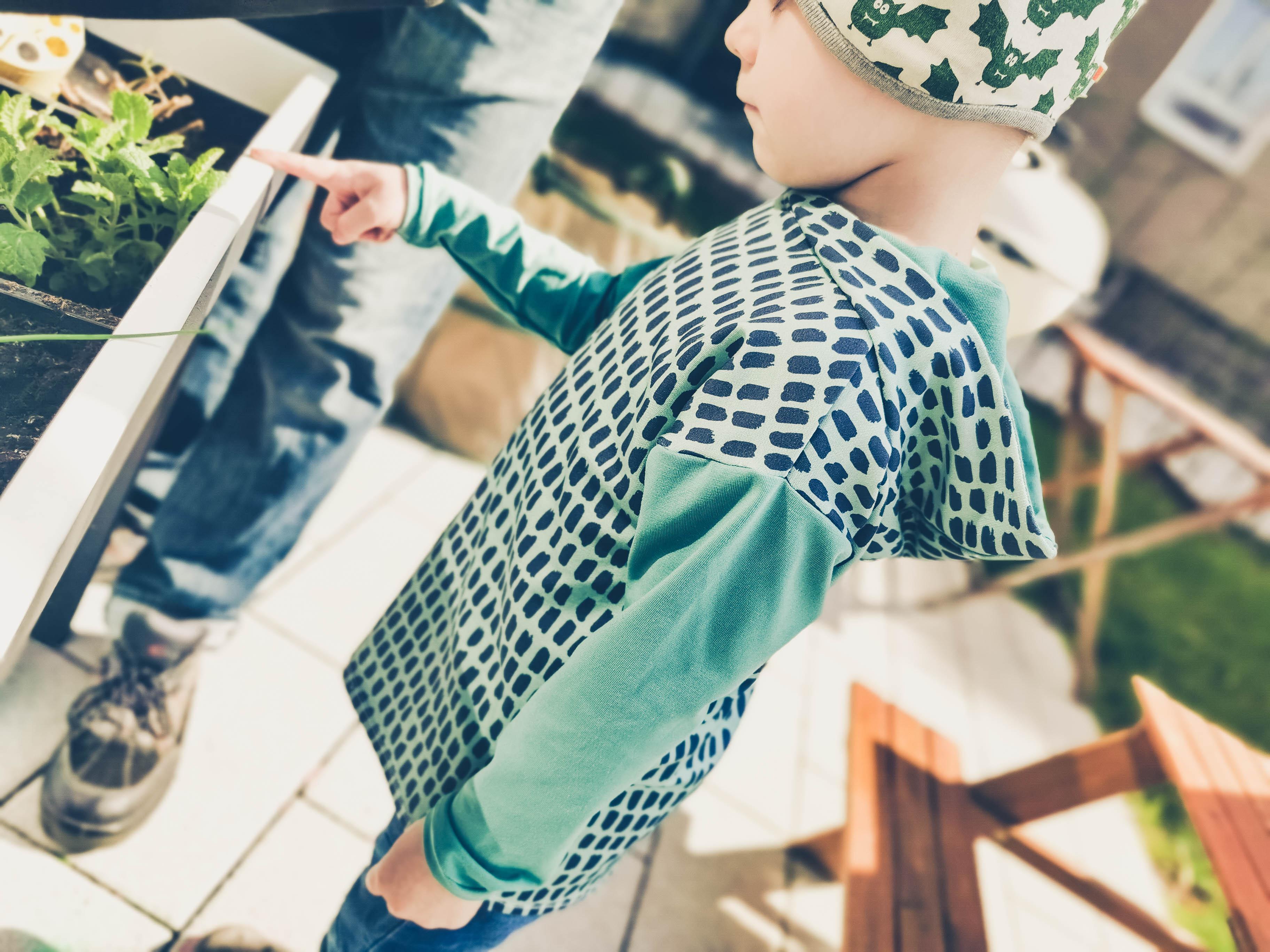 Kind in Longsleeve Mitty mit Kapuze zeigt auf Hochbeet